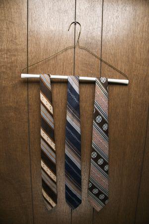 holzvert�felung: Drei Retro-Bindungen an einem Draht h�ngende Kleiderb�gel gegen Holzvert�felung. Lizenzfreie Bilder