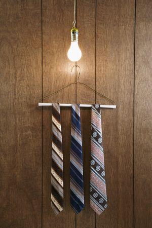 holzvert�felung: Drei Retro-Bindungen h�ngen auf einem Draht-Kleiderb�gel gegen Holzt�felung mit einem leuchtenden Gl�hbirne h�ngt von oben.