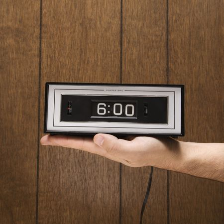 against the clock: Caucasion male hand holding retro clock set for 6:00 against wood paneling.
