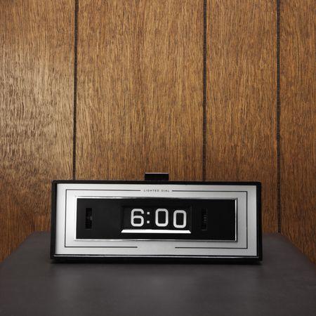 Retro clock set for 6:00 against wood paneling.