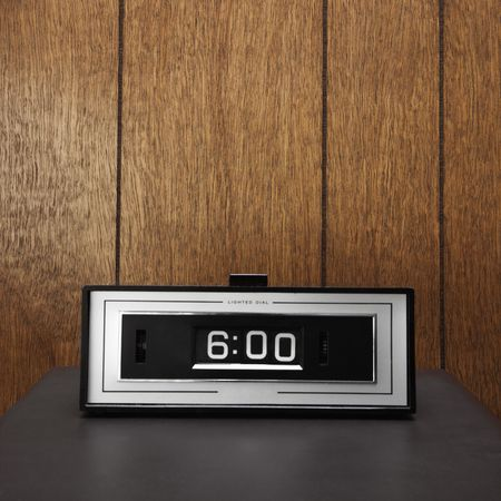 against the clock: Retro clock set for 6:00 against wood paneling.