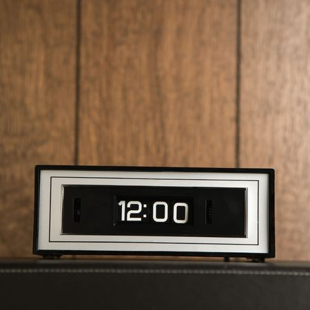 Retro clock set for 12:00 against wood paneling. Stock Photo - 1906719