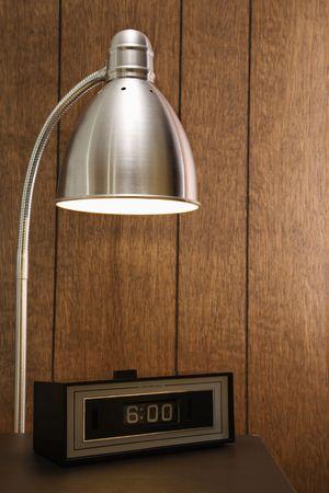 Retro scene of desk lamp shining on retro clock set for 6:00 against wood paneling. Stock Photo - 1906624