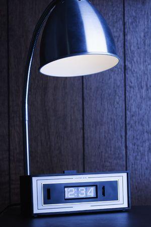 holzvert�felung: Desk Lampe auf Retro Uhr gegen Holz Verkleidung. Lizenzfreie Bilder