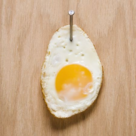 nailed: Fried egg nailed to wood. Stock Photo