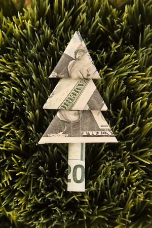 Studio shot of origami tree made from a twenty dollar bill placed in grass. photo