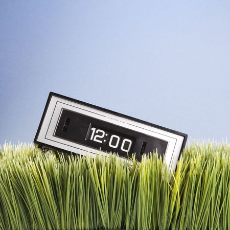 placed: Studio shot of retro alarm clock placed in grass.