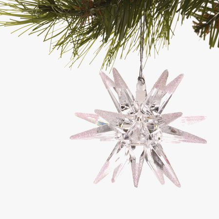 Still life of star-shaped white Christmas ornament hanging from pine branch. Stock Photo - 1906754