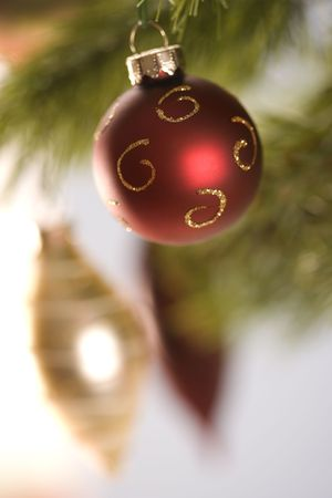 Still life of red and gold Christmas ornaments hanging from pine branch. photo