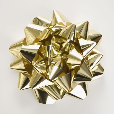 customs and celebrations: Still life of big shiny gold Christmas bow.