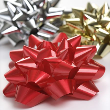 Still life of big shiny red, gold and silver Christmas bows. photo
