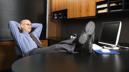 office desk: Caucasian middle-aged businessman in office sitting with feet on desk.