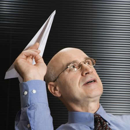 Caucasian middle-aged businessman playing with paper airplane. photo