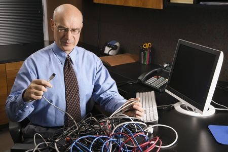 chaos: Caucasian middle-aged businessman at desk in office with a tangle of computer cables.
