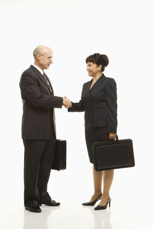 eachother: Caucasian middle-aged businessman and Filipino businesswoman standing looking at eachother shaking hands against white background.