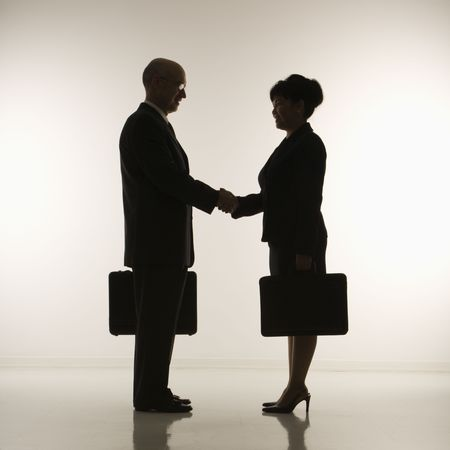 Caucasian middle-aged businessman and Filipino businesswoman standing looking at eachother shaking hands against white background. photo