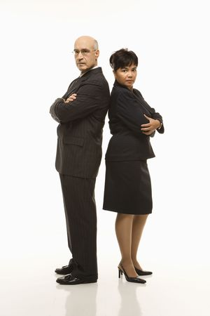 sexes: Caucasian middle-aged businessman and Filipino businesswoman standing back to back with arms crossed looking serious.