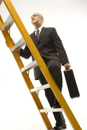 Caucasian middle-aged businessman climbing ladder carrying briefcase. photo