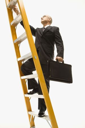 corporate ladder: Caucasian middle-aged businessman climbing ladder carrying briefcase.