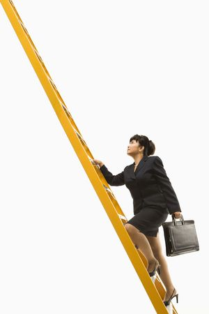 corporate ladder: Filipino middle-aged businesswoman climbing ladder carrying briefcase.