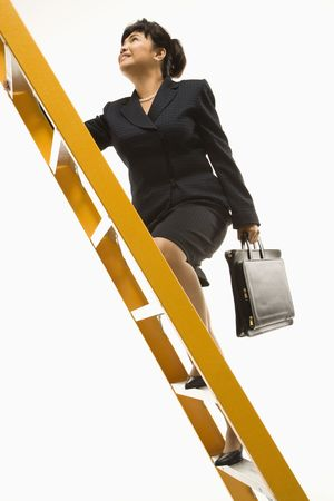 Filipino middle-aged businesswoman climbing ladder carrying briefcase. photo