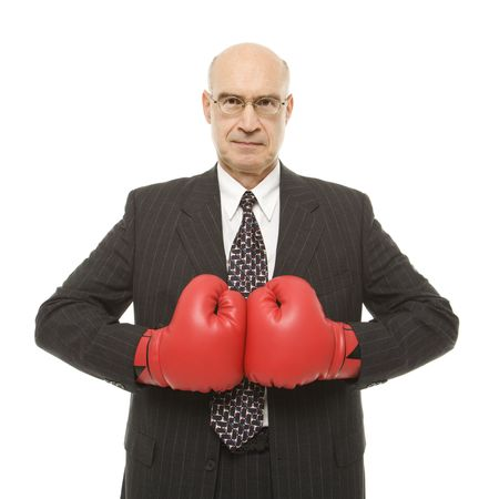 Caucasian middle-aged businessman wearing boxing gloves. photo