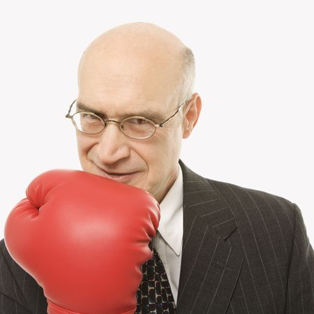 Caucasian middle-aged businessman holding up arm wearing boxing glove. photo