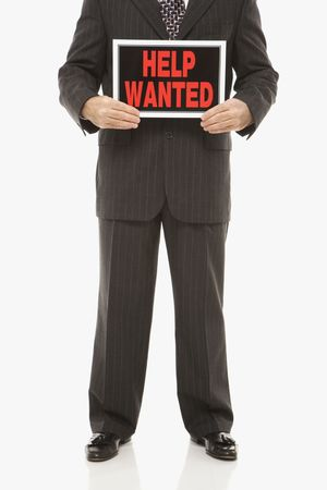 Caucasian middle-aged businessman holding help wanted sign. photo