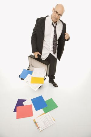 disheveled: Caucasian middle-aged businessman looking disheveled holding open briefcase with papers falling out. Stock Photo
