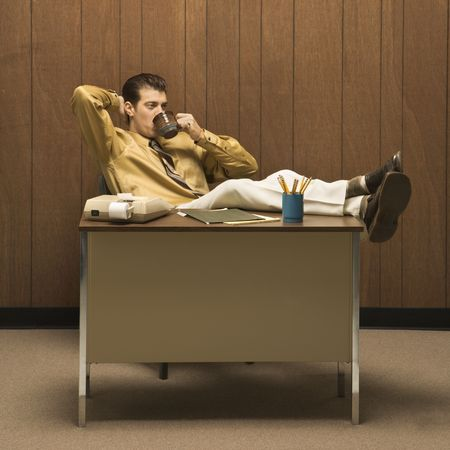 slacker: Caucasion mid-adult retro businessman sitting with feet propped on desk leaning back with hand behind head drinking coffee. Stock Photo