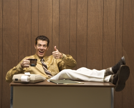 slacker: Caucasion mid-adult retro businessman sitting with feet propped on desk drinking coffee giving a thumbs up.
