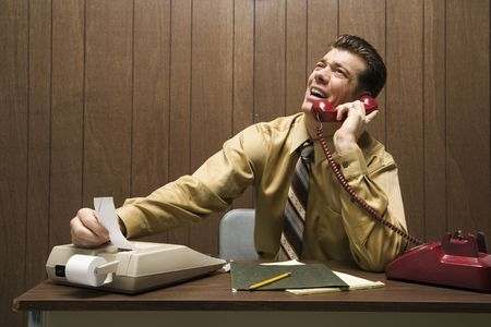 Caucasion mid-adult retro businessman sitting at desk talking on telephone using adding machine. photo