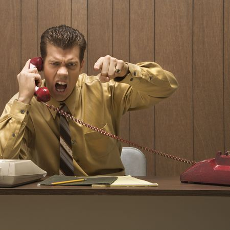 Caucasion mid-adult retro businessman sitting at desk talking on telephone with angry expression and gesture. photo