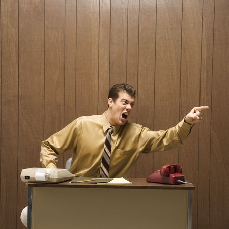 disgruntled: Caucasion mid-adult retro businessman sitting at desk pointing in anger.