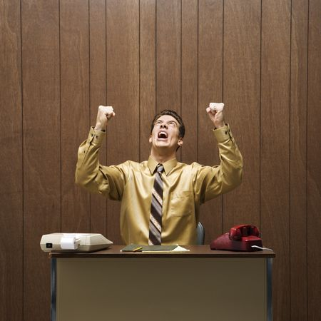 Caucasion mid-adult retro businessman sitting at desk raising fists in anger. photo