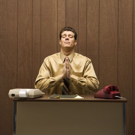 Caucasion mid-adult retro businessman sitting at desk praying in gratitude. Stock Photo - 1960396