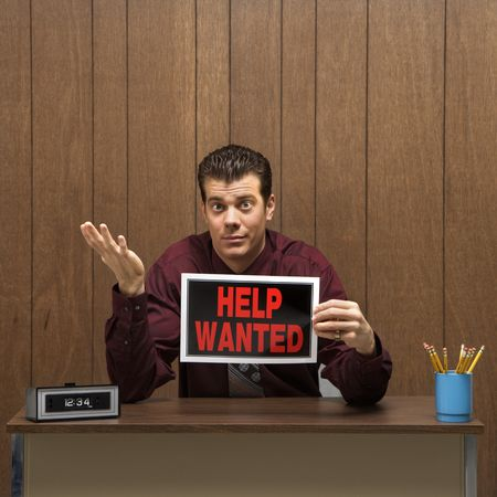 Caucasion mid-adult retro businessman sitting at desk holding help wanted sign with pleading expression. photo