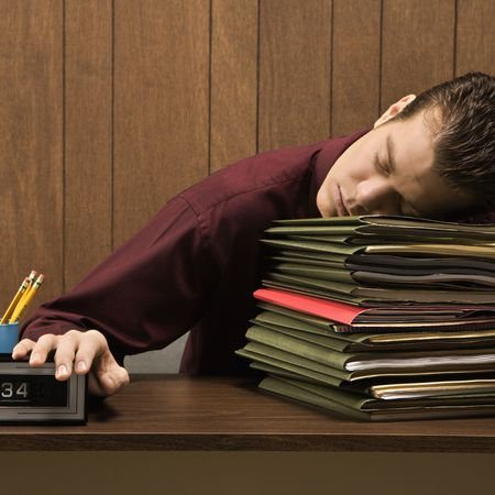 Caucasion mid-adult retro businessman sitting at desk with head down sleeping on a tall stack of folders. Stock Photo - 1960485