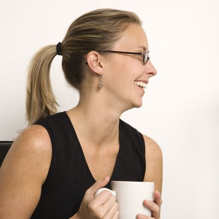 woman profile: Caucasian mid-adult woman wearing eyeglasses  holding coffee cup and looking to side.