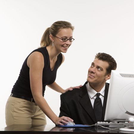 Caucasian mid-adult woman touching mid-adult man\'s shoulder\ and using mouse at computer.