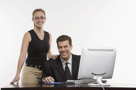 Caucasian mid-adult woman touching shoulder of man sitting at computer and looking at viewer. Stock Photo - 1991642