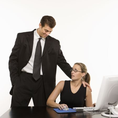uncomfortable: Caucasian mid-adult man touching shoulder of woman sitting at computer who feels uncomfortable. Stock Photo