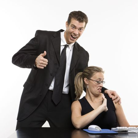Caucasian mid-adult man sexually harassing woman sitting at computer and giving thumbs up. photo