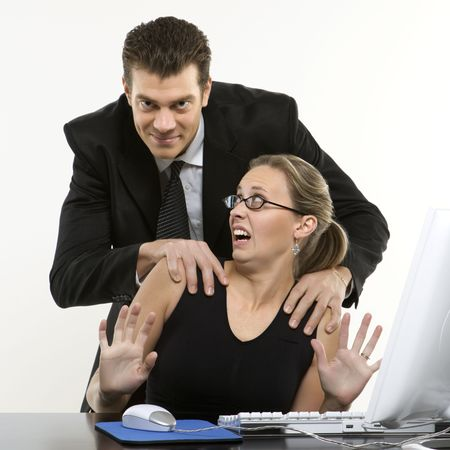 offend: Caucasian mid-adult man sexually harassing woman sitting at computer and looking at viewer. Stock Photo
