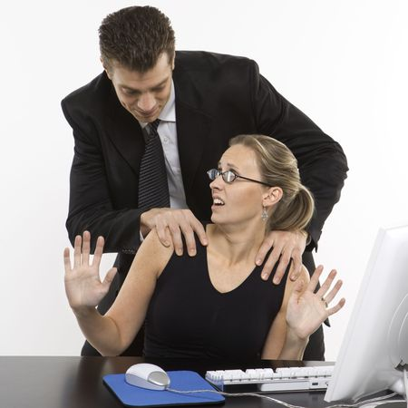 harassing: Caucasian mid-adult man sexually harassing woman sitting at computer.