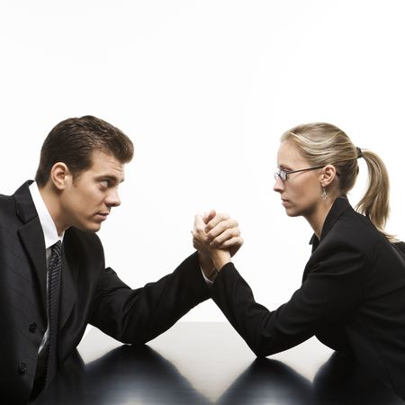 Side view of Caucasian mid-adult businessman and businesswoman arm wrestling on table. photo