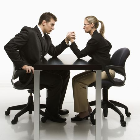 sexes: Side view of Caucasian mid-adult businessman and businesswoman arm wrestling on table.