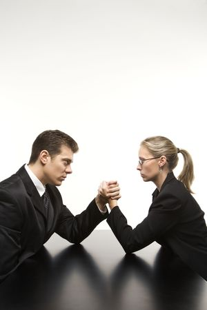 arm: Side view of Caucasian mid-adult businessman and businesswoman arm wrestling on table.