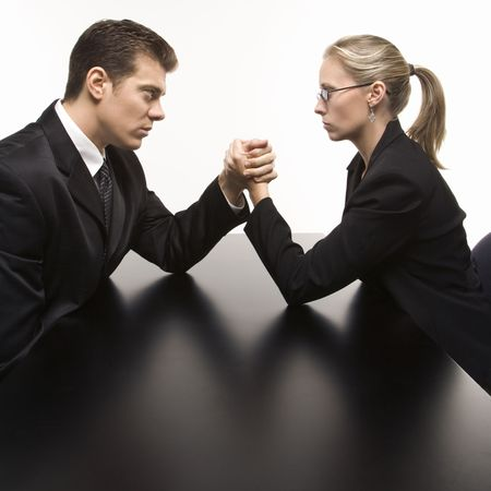 Side view of Caucasian mid-adult businessman and businesswoman arm wrestling on table. Stock Photo - 1991656