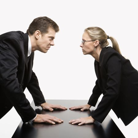Caucasian mid-adult businessman and woman staring at each other with hostile expressions. photo